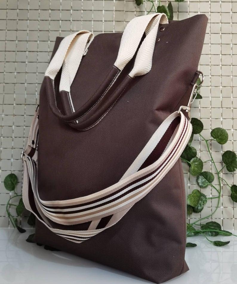 Bolso tote marrón impermeable de doble posición, bolso mensajero para días de lluvia.